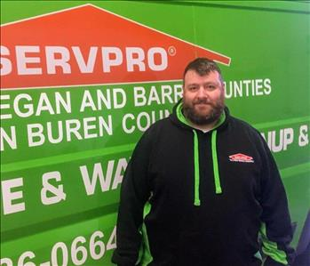 Male employee Manny standing in front of green SERVPRO van
